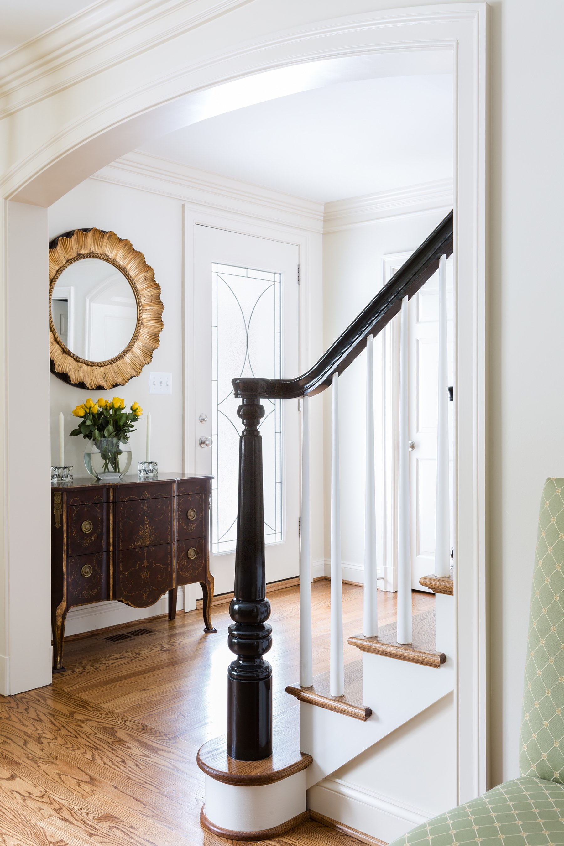 Home grand foyer with antiqued gold mirror and carved black stair newel post