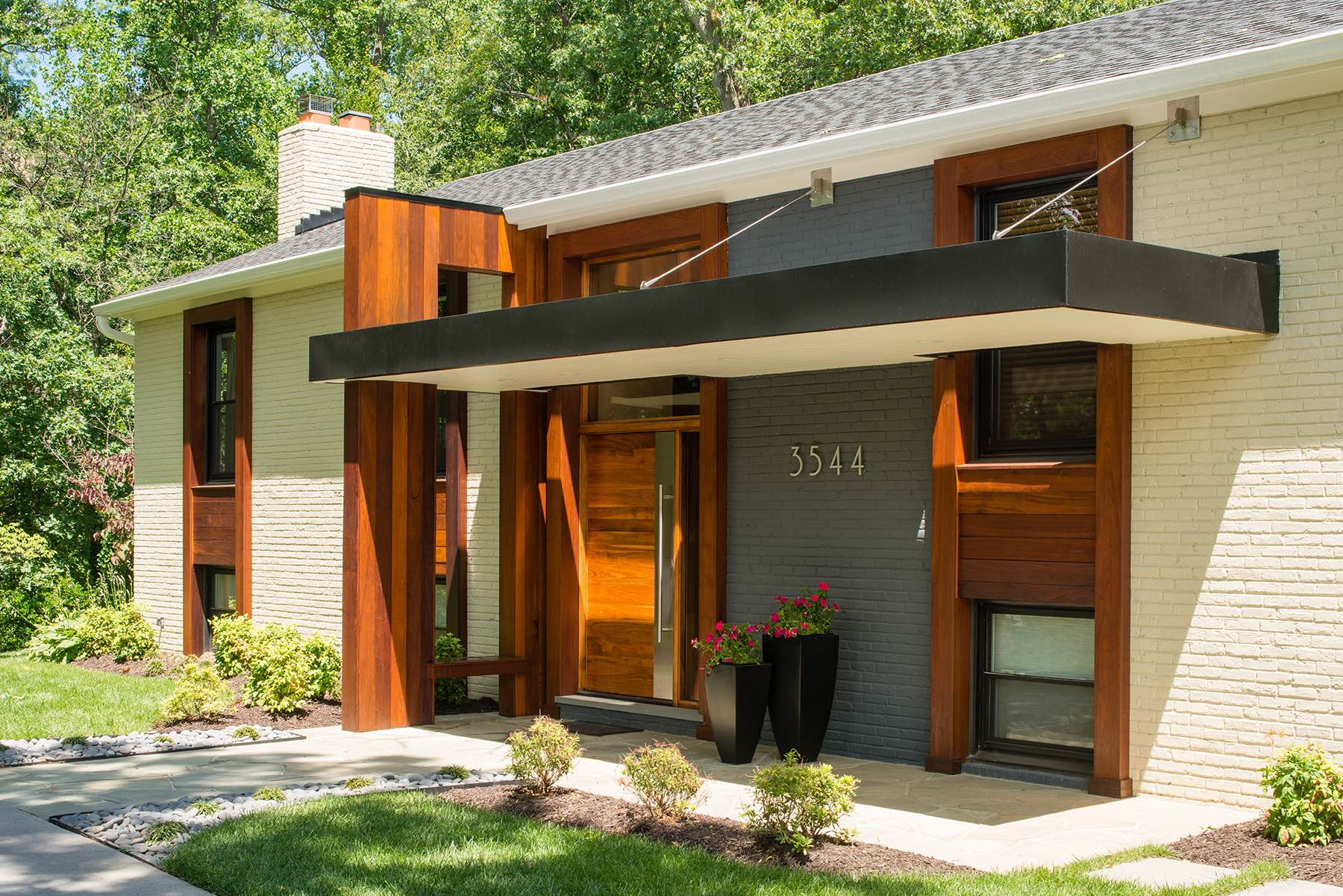 Contemporary home exterior with striking hanging portico and sculptural ipé wood