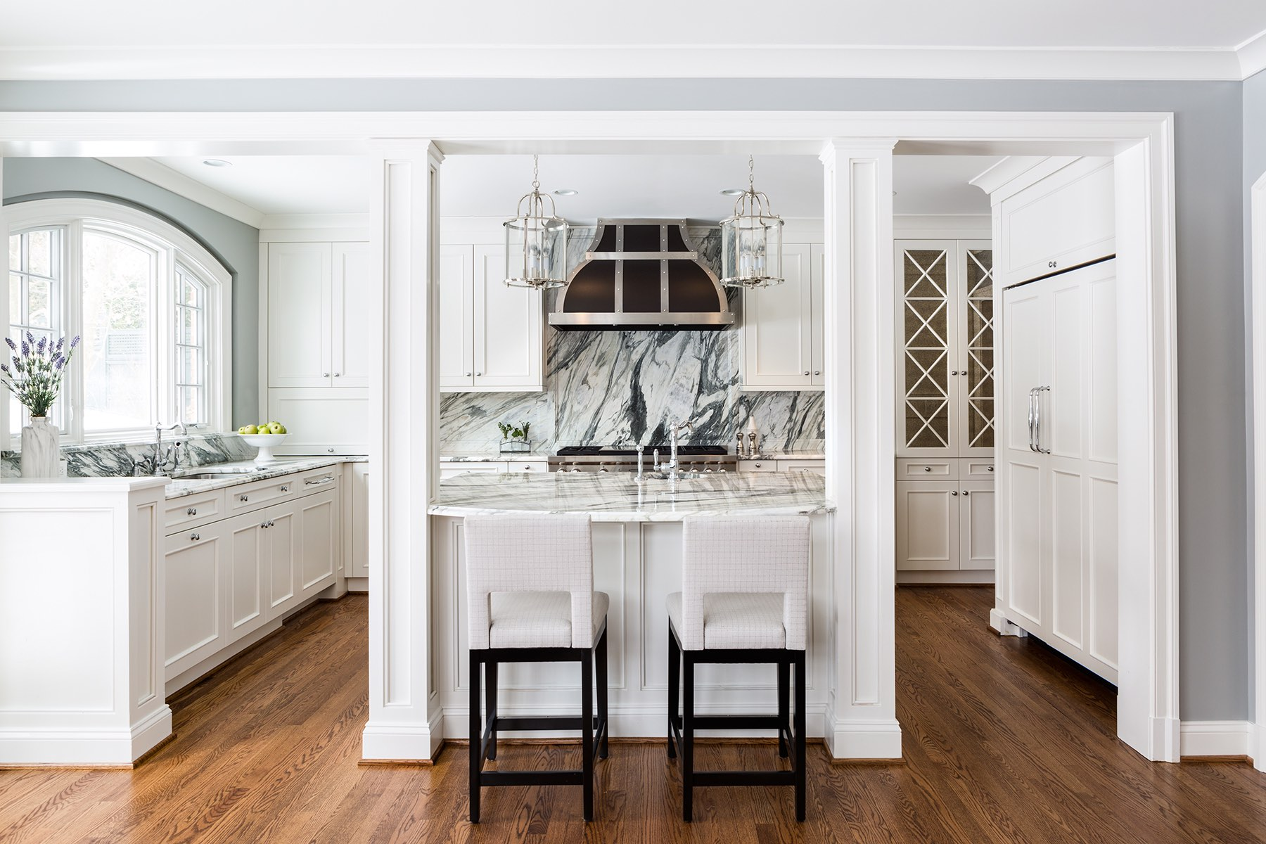 Custom kitchen with white cabinetry, white marble counters and island top, steel pendant lights