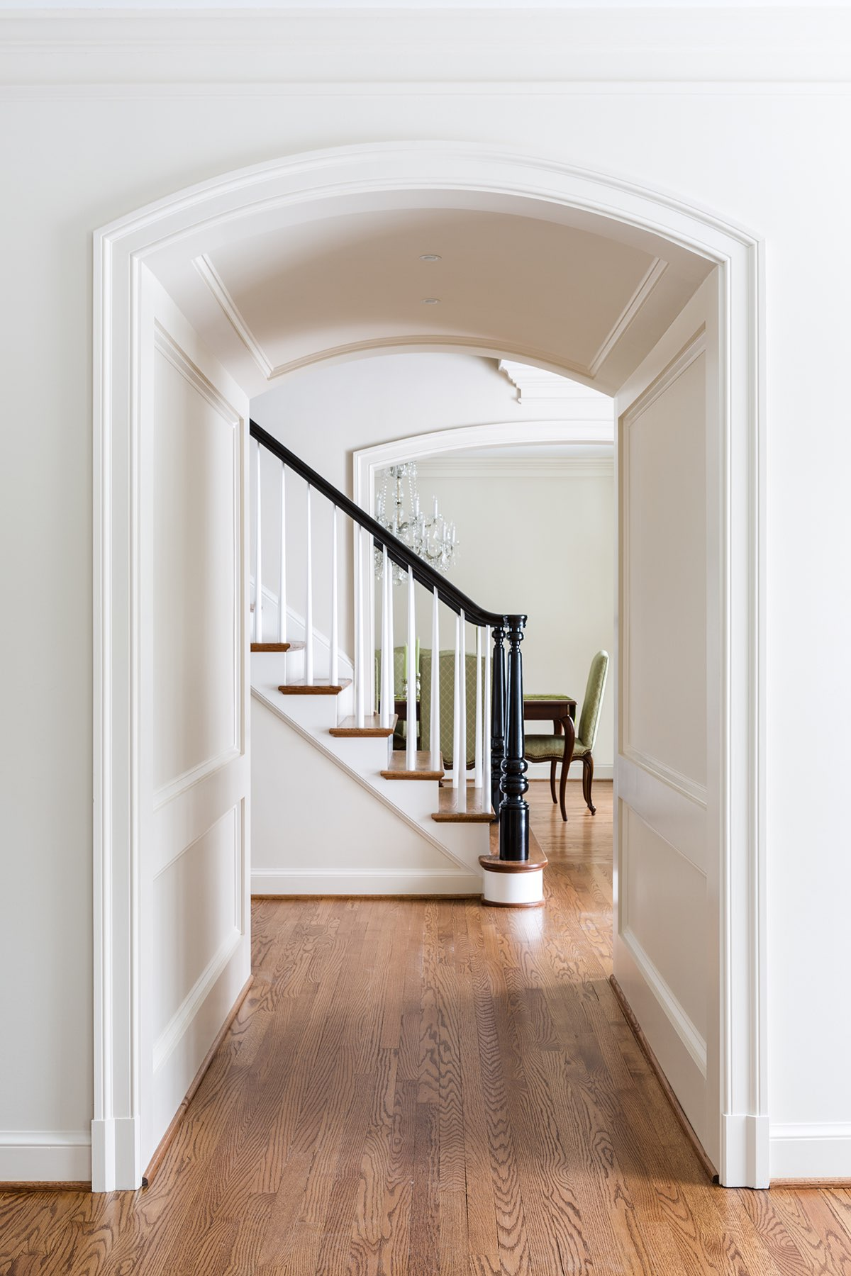 Custom hall archway and artisanal black paint finish on stairs