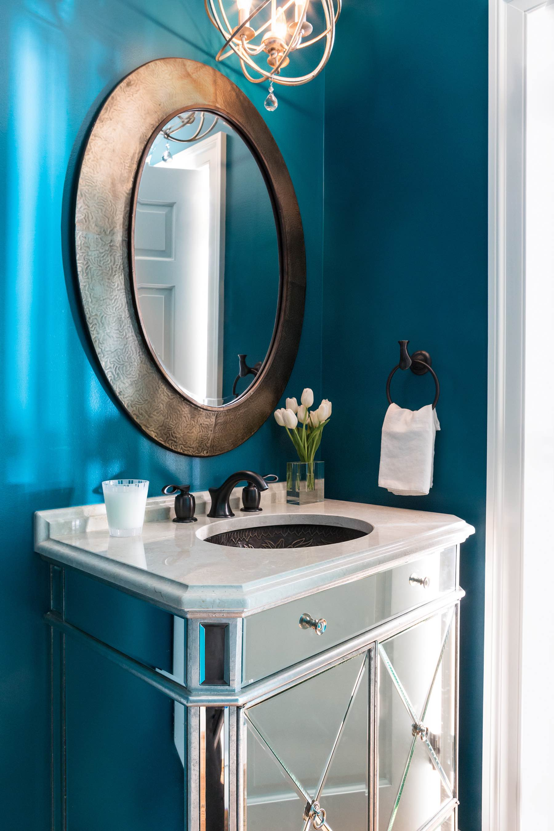 Powder room vanity with mirrored cabinets, teal high-gloss paint, marble vanity top, antiqued gold porthole mirror