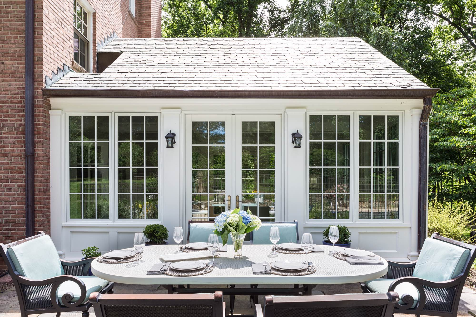 Dining table with bronze and celadon outdoor seating on sunny brick patio