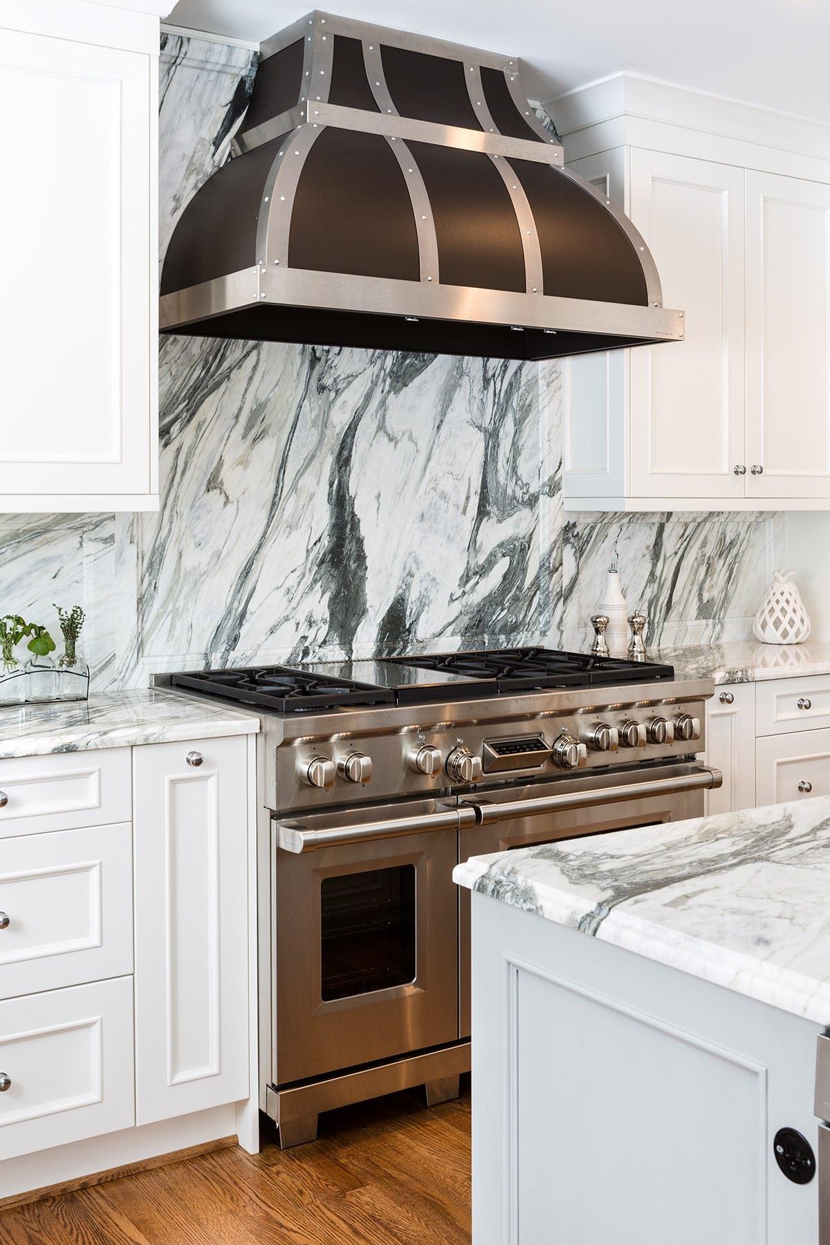 Home kitchen with stainless trim range hood, black-vein marble backsplash