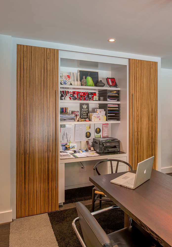 Sliding doors in striking zebrawood conceal an office niche