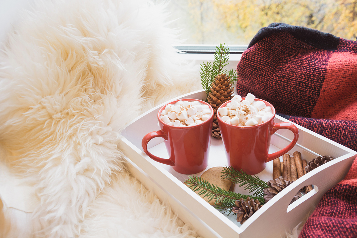 Two red cup of hot chocolate with marshmallow on white windowsill with furskin for rest. Holiday. Christmas morning. Romantic.