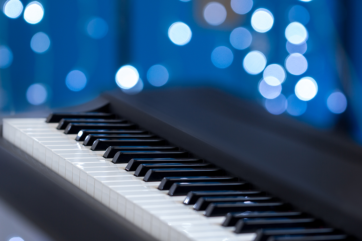 Piano keys side view with shallow depth of field on a blue bokeh background